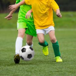 Kinder spielen Fußball auf einem Fußballplatz