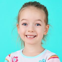 Mädchen lächelt und zeigt ersten verlorenen Milchzahn