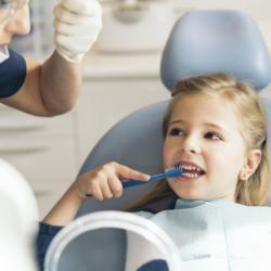 Junge Patientin übt Zähneputzen
