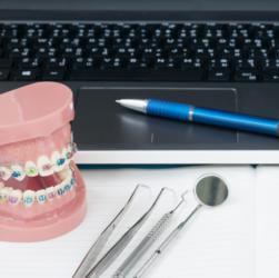 Zahnspangenmodell neben Laptop und Behandlungsinstrumenten