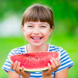 Mädchen mit Zahnspange isst ein Stück Wassermelone
