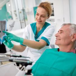 Fachkraft berät älteren Patienten beim Zahnarzt