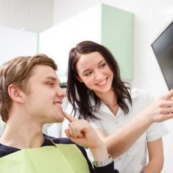 Zahnarzthelferin und Patient schauen auf Monitor