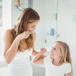 Mutter und Tochter putzen ihre Zähne