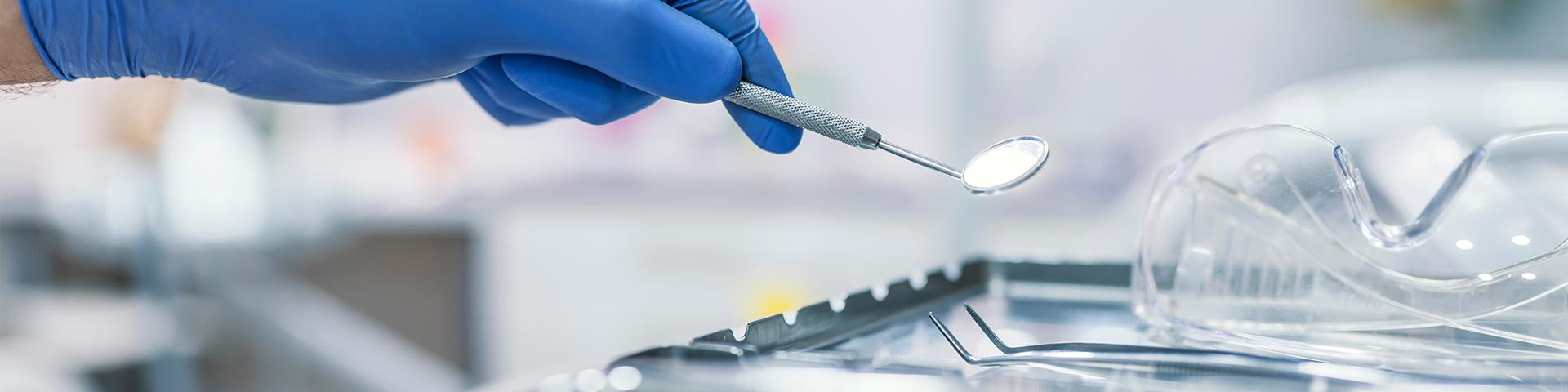 Hand hält Zahnarzt-Instrument