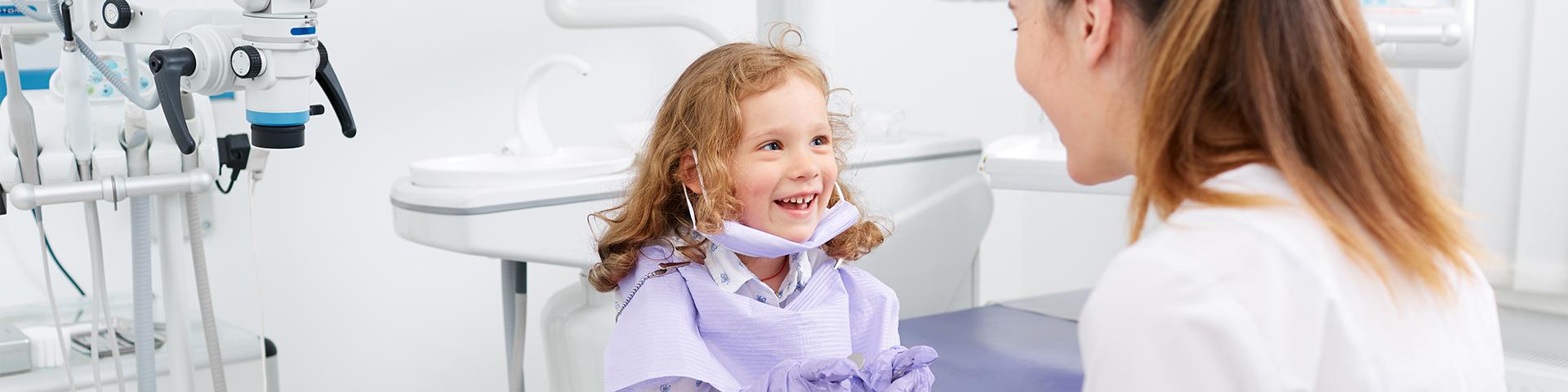 Kleines Mädchen lächelt sitzt auf Behandlungsstuhl und lächelt die Zahnärztin an