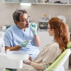 Zahnarzt erklärt Patientin die Behandlung