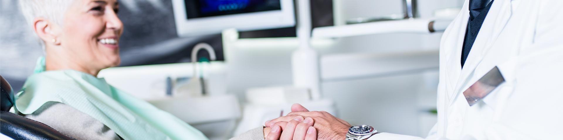 Zahnarzt hält Hand von älterer Patientin