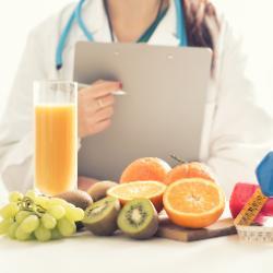 Ärztin mit Klemmbrett und gesundem Essen