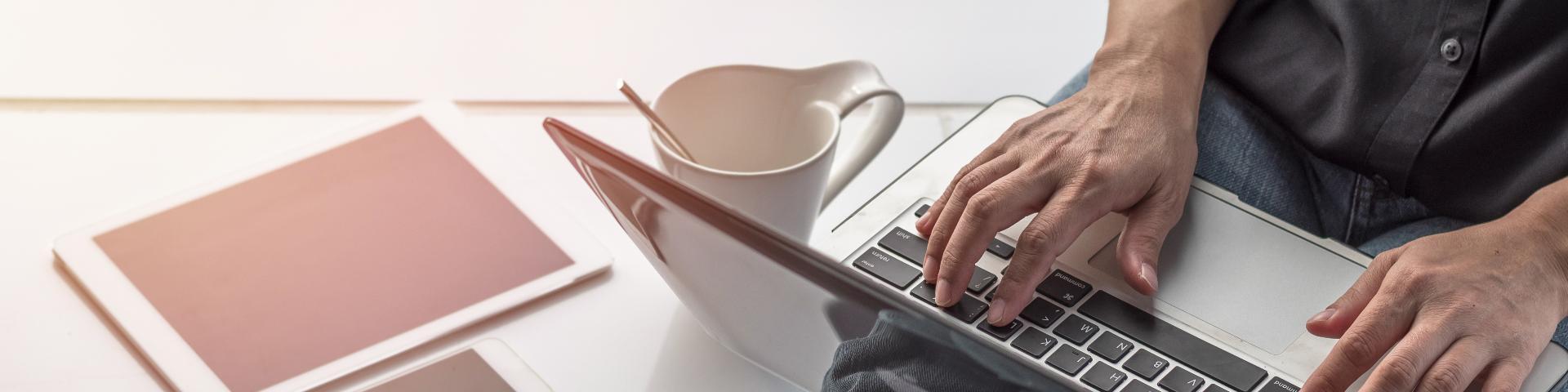 Mann mit Laptop , Tablet und Smartphone