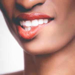 farbige Frau beißt sich auf die Lippe - Periimplantitis?