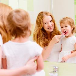Mutter hilft Kleinkind beim Zähneputzen/Zahnseide und Mundwasser