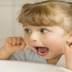 Kleines Mädchen benutzt Zahnseide