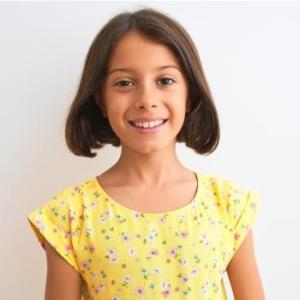 Lächelndes Mädchen mit gelbem Blumenkleid