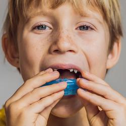 Junge setzt eine myofunktionelle Spange ein