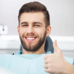Patient auf Zahnarztstuhl zeigt Daumen hoch