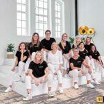 Dr. Wagenmann und sein Team bestehend aus 10 Personen sitzen auf einer weißen Treppe